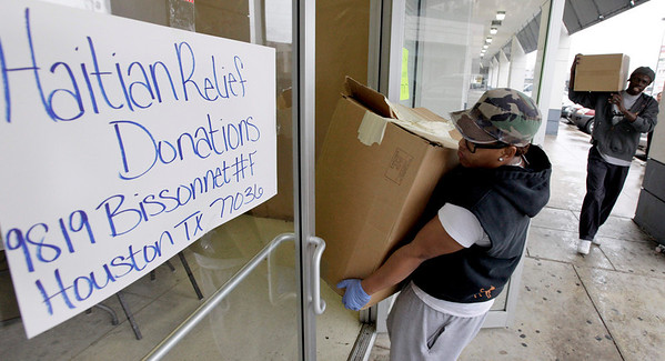 Volunteers Andrea Everline, left, and Gutenberg Pierre, right, carry donated items for the victims of the earthquake in Haiti at the Multi Ethnic Community Center Thursday, Jan. 14, 2010, in Houston. (AP Photo/David J. Phillip)