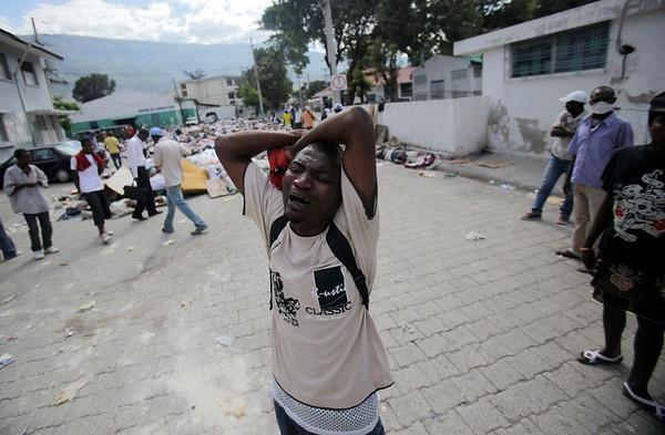 A man cries outside the morgue of the General Hospital in Port-au-Prince, Haiti, Thursday, Jan. 14, 2010.  A 7.0-magnitude earthquake struck Haiti Tuesday.  (AP Photo/Ariana Cubillos)