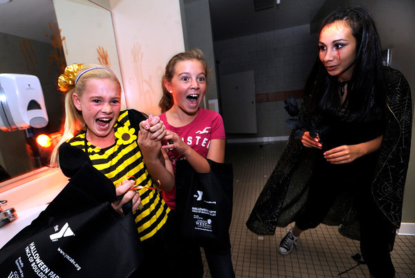 "Mahri Hereid, 10, at left and Sophie Moellenberg let out a scream as Bonnie Schrag jumps out from the darkness in the haunted house at the  Halloween Party at the Arapahoe Center YMCA in Lafayette. For more photos of the halloween party go to  <a href=""http://www.dailycamera.com"">http://www.dailycamera.com</a><br /> Photo by Paul Aiken Monday Oct 24, 2011"