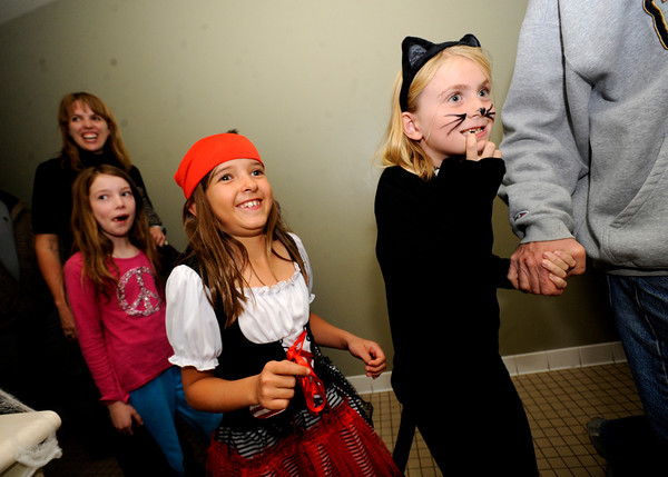 "Amanda Dombeck, 8, at right holds onto her dad's hand as she and her friend Riley Miller, dressed as a pirate, work their way through the haunted house at the Halloween Party at the Arapahoe Center YMCA in Lafayette. For more photos from the halloween party go to  <a href=""http://www.dailycamera.com"">http://www.dailycamera.com</a>.<br /> Photo by Paul Aiken Monday Oct 24, 2011"