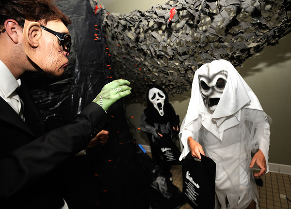"Marcus Godwin, lefts tries to scare Matthew Grant, 8, and Johnathan Grant, 11, at right, in the haunted house at the Halloween Party at the Arapahoe Center YMCA in Lafayette. For more photos from the halloween party go to  <a href=""http://www.dailycamera.com"">http://www.dailycamera.com</a>.<br /> Photo by Paul Aiken Monday Oct 24, 2011"