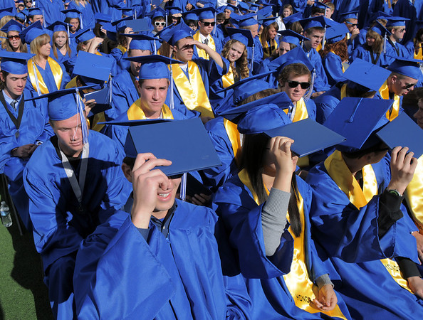 Graduates use their diplomas for shade during Saturday's Broomfield High School graduation ceremony at Elizabeth Kennedy Stadium.<br /> May 21, 2011<br /> staff photo/David R. Jennings