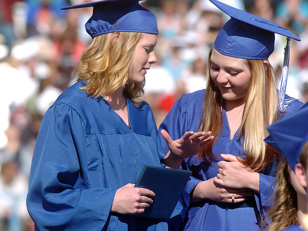 Abby Isles, left, shows  Kaitlyn Huston how steady her hands are during Saturday's Broomfield High School graduation ceremony at Elizabeth Kennedy Stadium.<br /> May 21, 2011<br /> staff photo/David R. Jennings