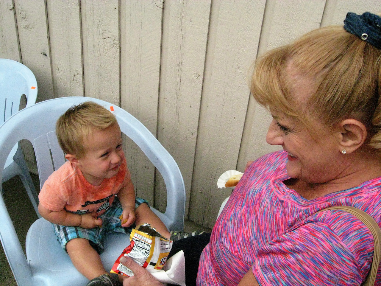 BOB SANDRICK / GAZETTE Henry Richlovsky, 1, of Mansfied munched on corn chips with grandmother Jackie Parente of Granger Township on Saturday during a shopping visit to ReStore at 342 East Smith Road in Medina.