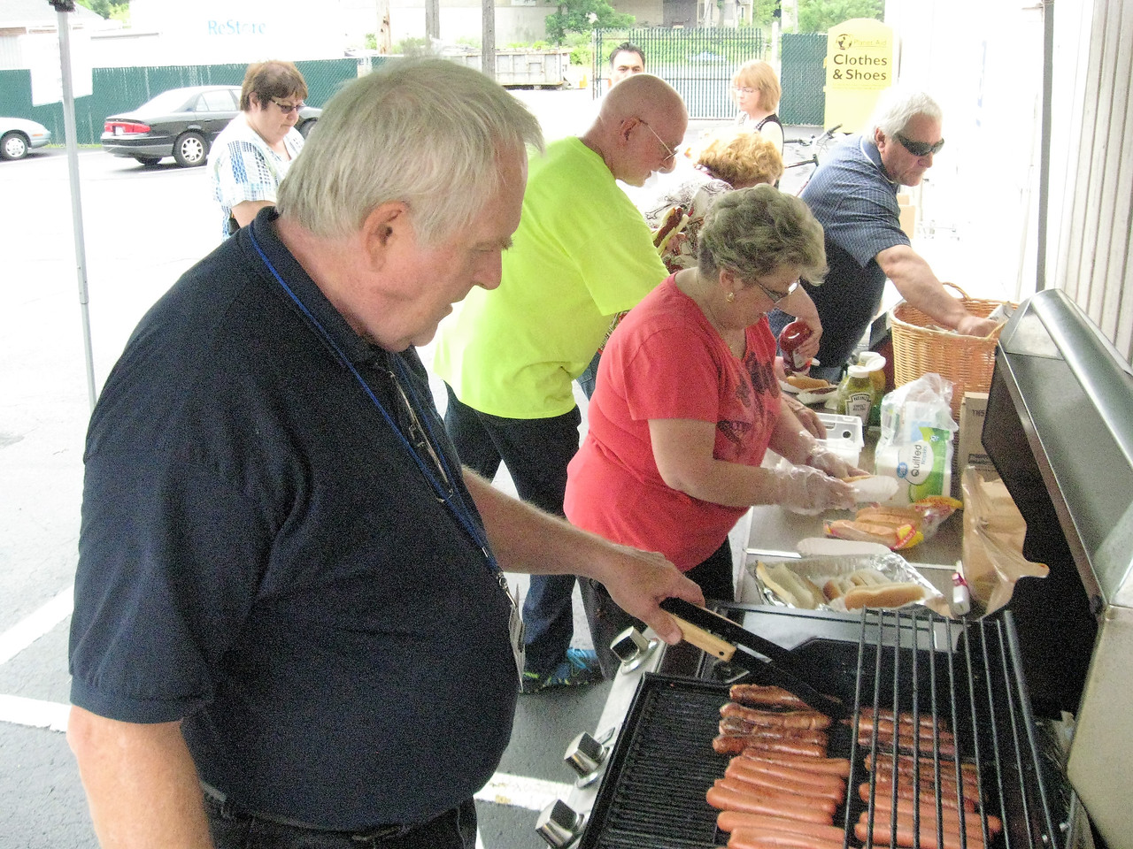 BOB SANDRICK / GAZETTE Jerry Barthelemy, assistant store manager, and volunteer Pat Neal grill and serve hot dogs for ReStore customers Saturday. It was the store's sixth anniversary on Smith Road in Medina.