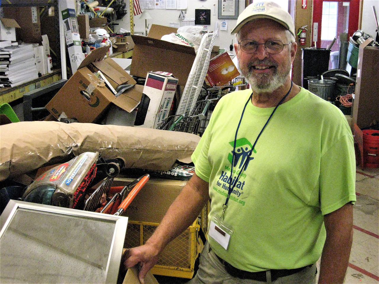 BOB SANDRICK / GAZETTE Dan Shumaker, ReStore manager at 342 East Smith Road in Medina, takes stock of recently received items on Saturday.