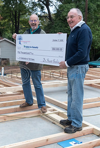 First Presbyterian Church pastor Rev. Dr. Stuart Baskin presents a check of $50,000 to Habitat for Humanity of Smith County CEO Jack Wilson during a wall raising on Shaw Street in Tyler on Saturday, Oct. 17, 2020. First Presbyterian Church is sponsoring this house, and their members will volunteer with the build.
