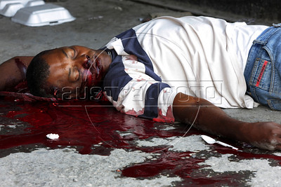 A man lies dead in downtown Port au Prince, Haiti, after shots were fired upon looters. Lawlessness remains in the city as the government is virtually non-existent. (Australfoto/Douglas Engle)
