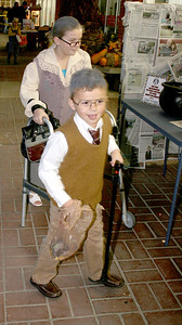 Megan, 10, and Brandon, 6, Stehle, dressed as an old lady and old man, make their way down the sidewalk aided by a walker and a cane during the Boone Village Halloween Party Tuesday evening, Oct. 29.