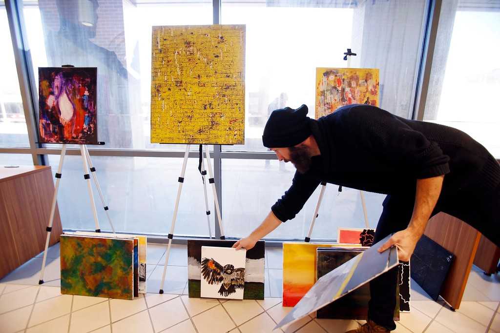 . Soldier On Art Director Nathan Hanford organizes and displays artwork by current and former Soldier On residents for the First Fridays Artswalk at the Veterans Transportation Center at the Intermodal Center in Pittsfield. Thursday, October 6, 2016. Stephanie Zollshan � The Berkshire Eagle | photos.berkshireeagle.com