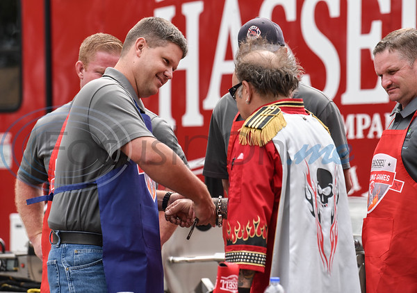 Jacksonville Police Captain Nathan Winship handcuffs Chef STRETCH to keep the judge from assisting contestants during the Hassell Cattle Company Grilling Games between the Jacksonville Police Department and the Jacksonville Fire Department.
