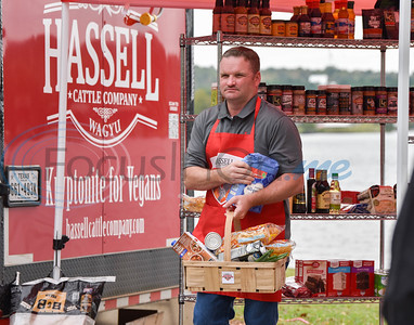 Jacksonville Fire Department Lieutenant David Glidewell carries the departments chosen ingredients back to the grilling station during the Hassell Cattle Grilling Games contest against the Jacksonville Police Department on Saturday.