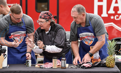 Handcuffed Chef Gail Huesmann (center) assists Jacksonville Police Captain Steven Markasky (left) and Jacksonville Police Chief Joe Williams (right) in a grilling contest against the Jacksonville Fire Department at Lake Jacksonville on Saturday.