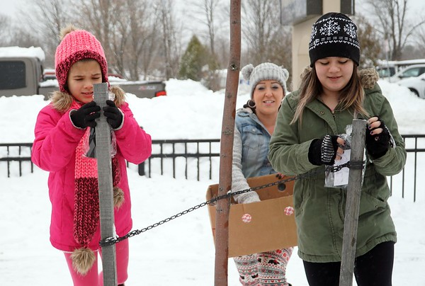 """BEN GARVER — THE BERKSHIRE EAGLE<br /> Karla Neff and her daughter Asena (green jacket) and friend Nevaeh Morse put hats and mittens out along North Street with a note saying """"Stay Warm in the Storm."""" Monday, December 2, 2019."""