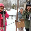 "BEN GARVER — THE BERKSHIRE EAGLE<br /> Karla Neff and her daughter Asena (green jacket) and friend Nevaeh Morse put hats and mittens out along North Street with a note saying ""Stay Warm in the Storm."" Monday, December 2, 2019."
