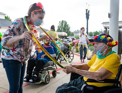 "The Waterton Healthcare and Rehabilitation at Shiloh certified occupational therapy assistant Shelby Jeter brings a hula hoop over to resident Curtis Williams during a Hawaiian-themed event in their parking lot on Friday, July 31, 2020 in Tyler. The afternoon event allowed residents and staff alike to get together to play games of ring toss, hula-hoop, limbo and ""punch the pineapple."" Special events at the center aim to bring joy to the residents and patients which have not been allowed to receive visitors inside the building since the end of March due to COVID-19."