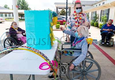 "The Waterton Healthcare and Rehabilitation at Shiloh resident Janie Sullivan plays a game called ""punch the pineapple"" during a Hawaiian-themed event in their parking lot on Friday, July 31, 2020 in Tyler. The afternoon event allowed residents and staff alike to get together to play games of ring toss, hula-hoop, limbo and ""punch the pineapple."" Special events at the center aim to bring joy to the residents and patients which have not been allowed to receive visitors inside the building since the end of March due to COVID-19."