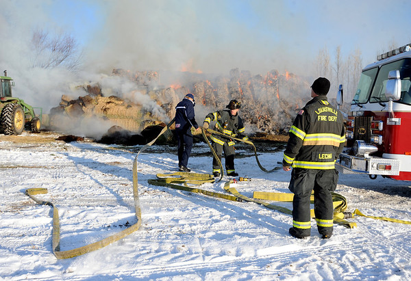 """Louisville firefighters prepare the water hose if it is needed.<br /> Louisville firefighters and the Colorado State Patrol monitor a hay stack fire  on Botany Lane, near Hwy 287 and Isabelle Road on Friday morning.<br /> For a video and more photos of the fire, go to  <a href=""""http://www.dailycamera.com"""">http://www.dailycamera.com</a>.<br /> December 16, 2011 / Cliff Grassmick"""