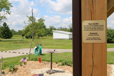LUCAS FORTNEY / GAZETTE Plaques donated by B&B Signs commemorate each of the four corners of the Heritage Farm's Children's Garden. The rain garden (shown in the background) was assembled using a mixture of sand, compost and traditional soil to capture rain water. Sixth-, seventh-, and eighth-grade students from nearby Visintainer Middle School planted prairie plants native to Northeast Ohio with deep roots that complement the soil and allow for more efficient water collection.