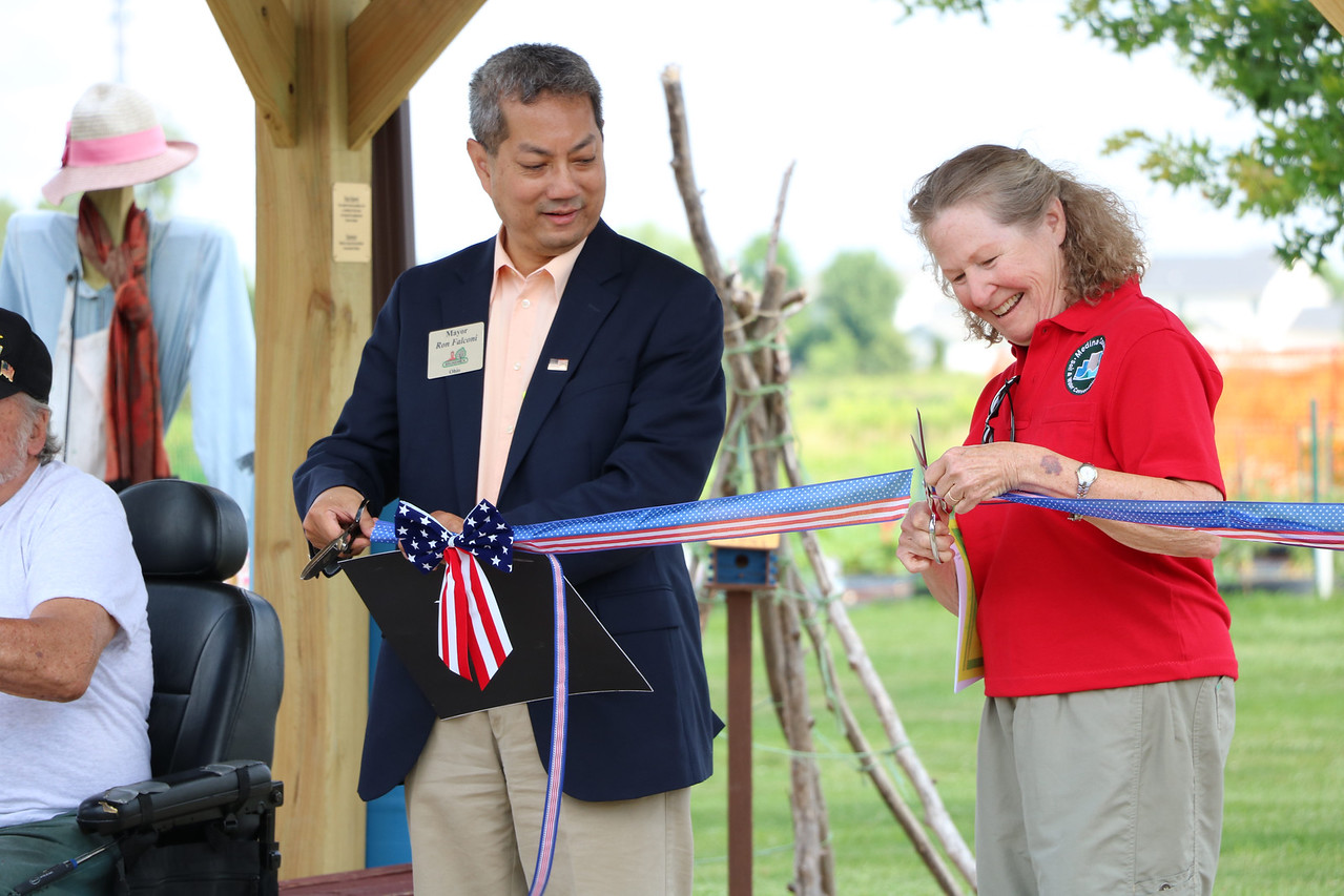 LUCAS FORTNEY / GAZETTE Brunswick Mayor Ron Falconi (left) and Education Specialist Beth Schnabel cut a ribbon in a ceremony Saturday at the at the Brunswick Heritage Farm's Children's Garden.