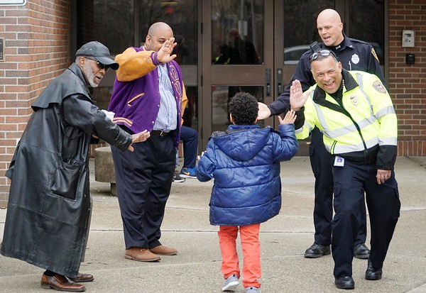 BEN GARVER — THE BERKSHIRE EAGLE<br /> Dennis Powell, Warren Dews, Officer Darren Derby and Chief Michael Wynn give high-fives to students entering Conte Community on the last day of school before spring break.