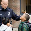 BEN GARVER — THE BERKSHIRE EAGLE<br /> Officer Darren Derby visits with children at Conte Community School on the Friday before vacation.