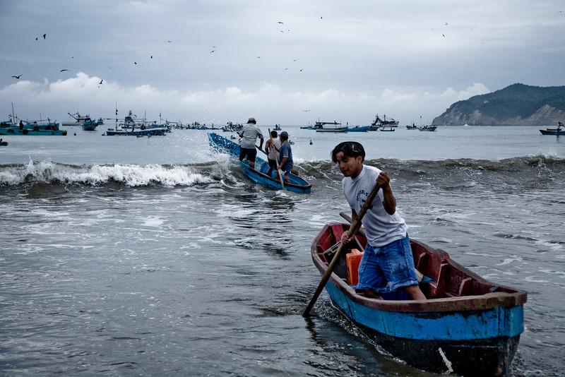Puerto Lopez. Fisherman reaching their fishing boat.<br /> <br /> Un groupe de pêcheurs rejoignent leur embarcation depuis une petite plage du village de puerto lopez  en Équateur<br /> Photo Olivier PontBriand