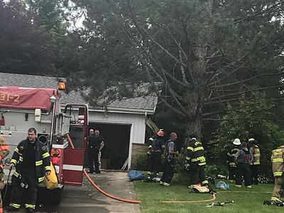 Hinckley firefighters, with the help of other first responders, work to get a house fire at 1714 Sofia Lane under control Monday afternoon. Siding can be seen hanging off of the side of the home due to the fire. ALYSSA ALFANO / GAZETTE