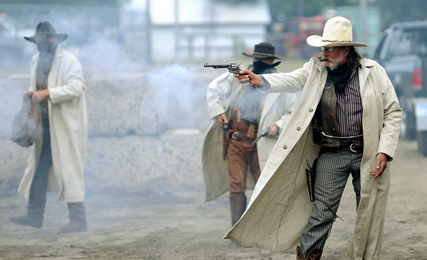 The bad guys are enveloped in a cloud of gunsmoke as they shoot it out with the local sheriff during a re-enactment on Saturday at the Nicollet County Fair of at attempt by the Sontag-Evans gang to rob a train between Kasota and St. Peter. The actual robbery attempt ocurred on July 1, 1892. Photo by John Cross