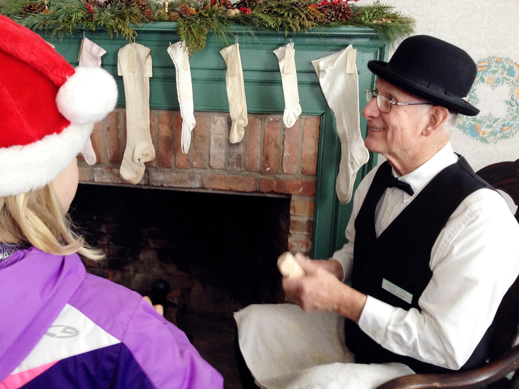 . Dick Kane, co-chair of collections at the Geauga County Historical Society, tells a group of children of the wooden doll he�s carving while in character as a person from the mid-1800s, during a 2013 Christmas program at Century Village. (News-Herald file)