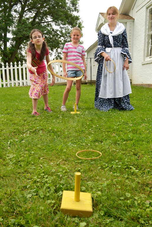 """. Beth Pierce, left, of Huntsburg, watches her ring\'s flight as she plays \""""Cuoits,\"""" a ring toss game, with Holly Englert, of Burton, and volunteer Olivia Hoffman at the Geauga County Historical Society�s Pioneer School 2014 at Century Village Museum in Burton Village. (News-Herald file)"""