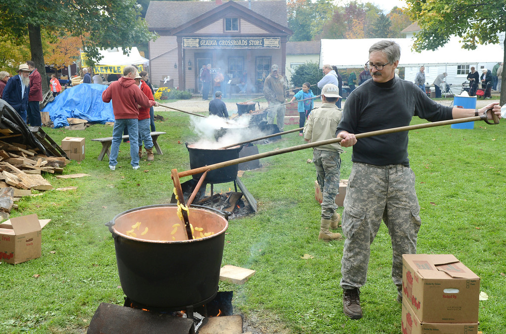 . Volunteers stir kettles of apple syrup, apple cider, and apples that will condense to apple butter in about four hours at the 2014 Annual Apple Butter Festival in Century Village.
