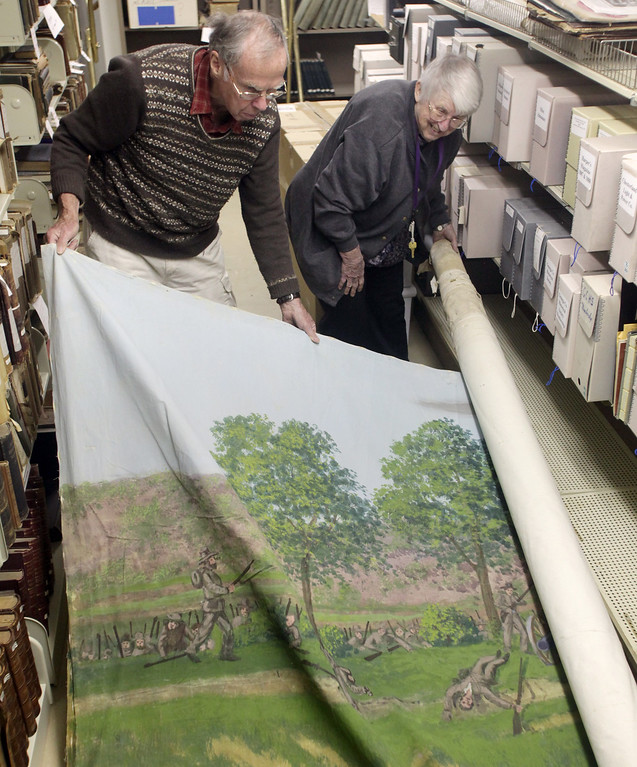 . Century Village volunteers Wayne Hosmer of South Russell and Teeter Grosvenor of Claridon Township unroll a giant art on canvas depicting a Civil War scene, which was re-discovered in the basement of the Shanower Library. The artwork was on display for the 2011 Civil War Re-Enactment Century Village. (News-Herald file)