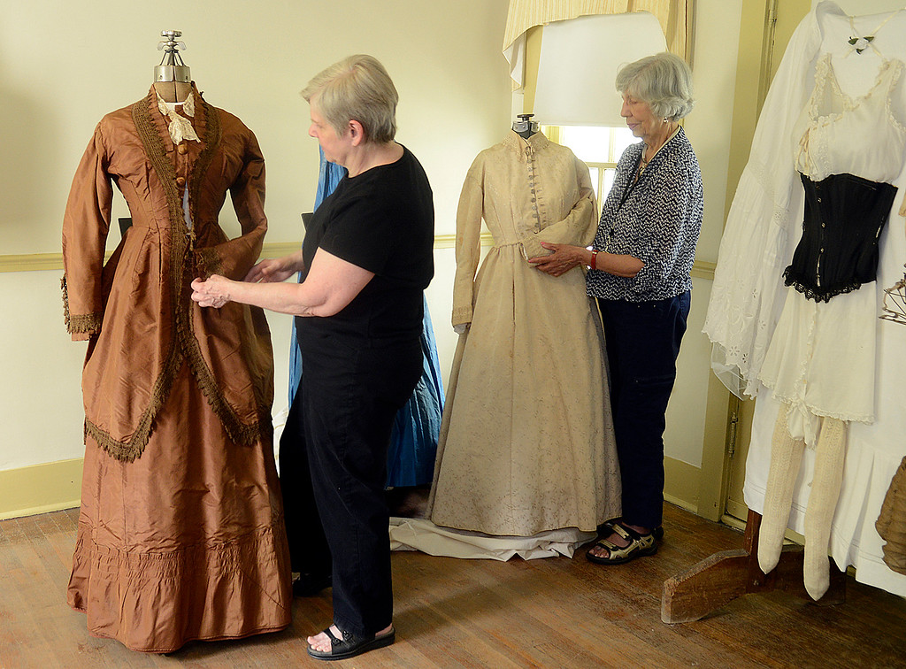 . Ann Thomas, left, and Carmen Kulgose set up A Century of Wedding Dresses exhibit at Century Village in Burton in 2014. The dresses date from 1840 to to 1950. (News-Herald file)