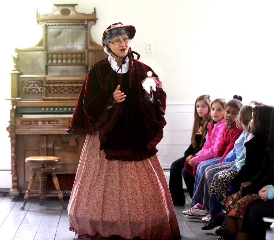 . Janet Kapela, a historical interpretor for Burton\'s Century Village talks with elementary school students on a field trip inside the Auburn Church at Century Village in 2011. (News-Herald file)