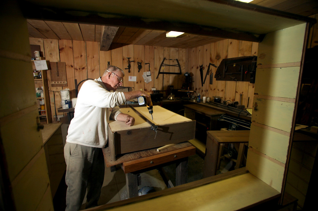 . Volunteer wood worker Dick Kane of Tompson Township assembles a cabinet for the remodeled Crossroads Store at Century Village in Burton in 2011. (News-Herald file)
