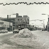 Photo provided by Lorain Historical Society <br> A car maneuvers around a snow pile, with holiday decorations hung in downtown Lorain.