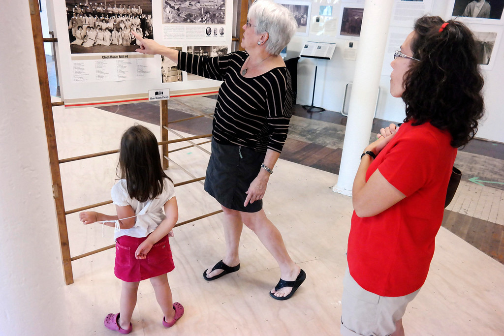 """. Gail Sellers tells the story of one of the children who worked in the Berkshire Mills in Adams at an exhibit called \""""The Mill Children\"""" at the 5 Hoosac Street Gallery.  Abigail Kunzmann, 6, and her mother Michelle in the foreground. Wednesday Aug 6, 2014. Ben Garver / Berkshire Eagle Staff / photos.berkshireeagle.com"""