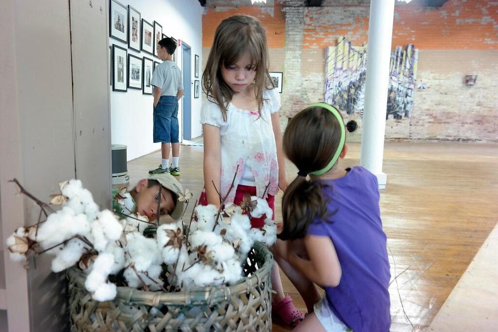 ". Abigail Kunzmann, 6, examines cotton at an exhibit called \""The Mill Children\"" in Adams.  Wednesday Aug. 6, 2014. Ben Garver / Berkshire Eagle Staff / photos.berkshireeagle.com"