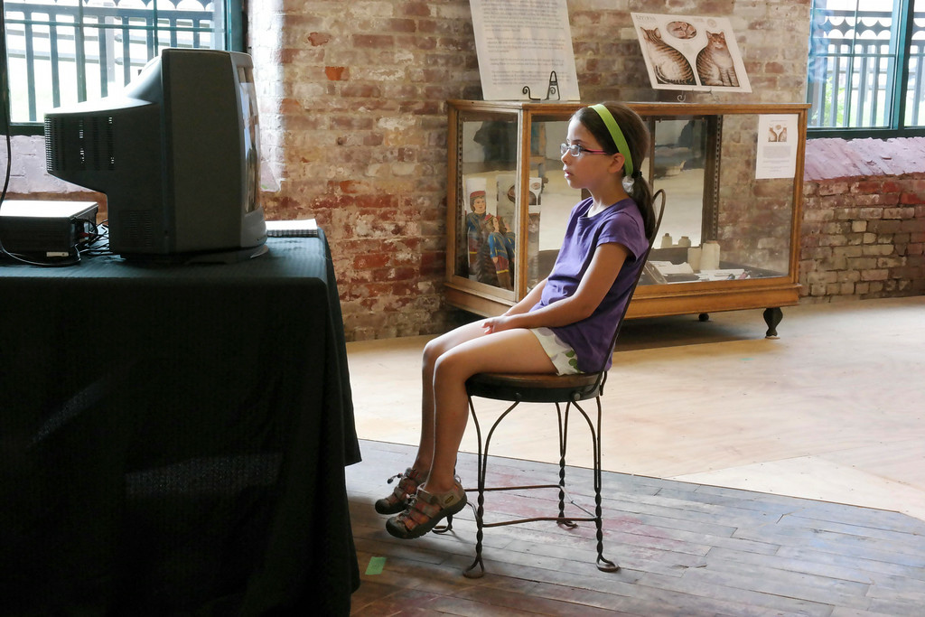 ". Sarah Kunzmann, 8, watches a video in \""The Mill Children\"" exhibit at the 5 Hoosac Street Gallery in Adams.  Wednesday Aug. 6, 2014. Ben Garver / Berkshire Eagle Staff / photos.berkshireeagle.com"