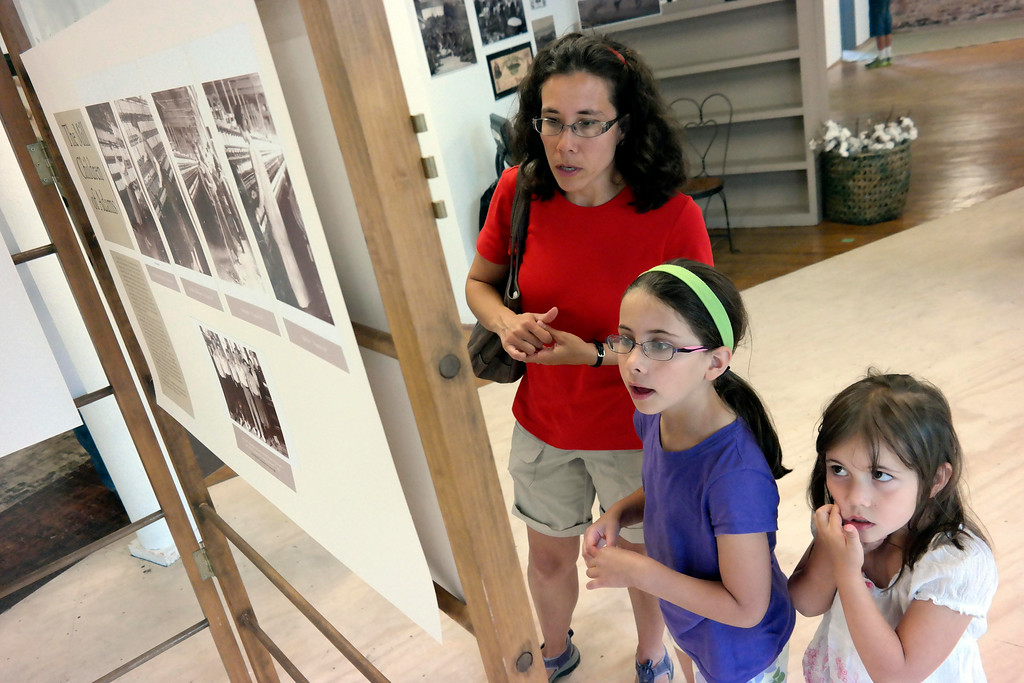 . Michelle Kunzmann talks to her daughters Sarah, 8, and Abigail, 6, about an exhibit about life in the mills at the 5 Hoosac Street Gallery in Adams.  Wednesday Aug. 6, 2014.  Ben Garver / Berkshire Eagle Staff / photos.berkshireeagle.com