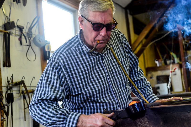 KRISTOPHER RADDER — BRATTLEBORO REFORMER<br /> DuGrenier uses a tube to slowly blow air into the glass ornament while using a shaping tool to keep it round.