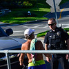 KRISTOPHER RADDER — BRATTLEBORO REFORMER<br /> Members of the Brattleboro Police Department escort a man who stopped his vehicle and started shouting at people that were involved in the Homeless Revolution outside the Municipal Building, in Brattleboro, away from the protest on Friday, Aug. 9, 2019.