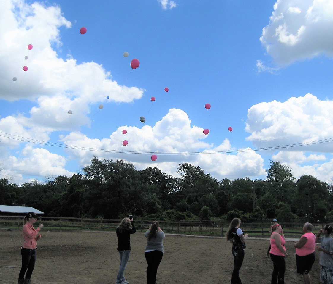 BOB SANDRICK / GAZETTE  Family members and friends of Kelli Baker; Michael Funk, who died in a motorcycle crash last year; and the Ulferts family of Homerville, who recently lost a horse, released balloons Saturday during the Kelli's C.R.U.S.A.D.E. horse show at the Medina County Fairgrounds.