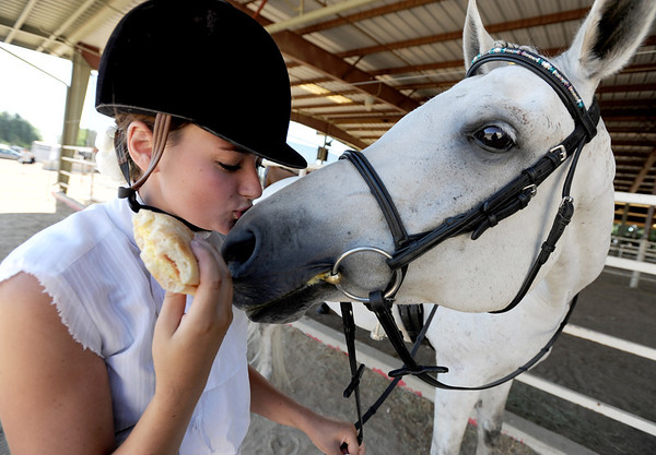 """Toni Bellitt, of Boulder, kisses her horse, Sonatta, while trying to keep her sandwich  from her hungry companion during  English showmanship on Thursday at the Boulder County Fair in Longmont.<br /> For more photos and video of horses, go to  <a href=""""http://www.dailycamera.com"""">http://www.dailycamera.com</a>.<br /> Cliff Grassmick / July 28, 2011"""