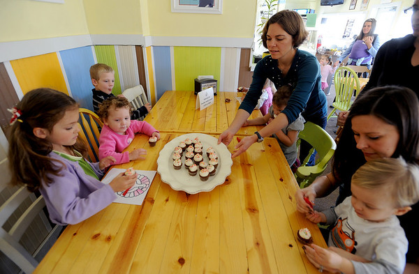"Hannah Grosser serves cupcakes to the kids in the play group, Malia, Grosser, left,  Helen Ploran, Curran Hassenstab, mom, Karen Wilder and son, Aiden, 19-months.<br /> Members of Boulder Moms Connect held a play date at Eats and Sweets with the theme of etiquette and technology.<br /> For a video and photos of the play date, go to  <a href=""http://www.dailycamera.com"">http://www.dailycamera.com</a>.<br /> Cliff Grassmick / November 18, 2011"