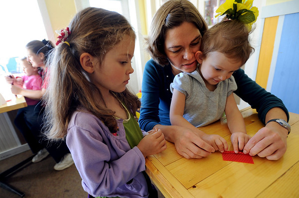 "Hannah Grosser helps her daughter Addie, 3, make a candle, while her other daughter, Malia, 5, watches her technique.<br /> Members of Boulder Moms Connect held a play date at Eats and Sweets with the theme of etiquette and technology.<br /> For a video and photos of the play date, go to  <a href=""http://www.dailycamera.com"">http://www.dailycamera.com</a>.<br /> Cliff Grassmick / November 18, 2011"