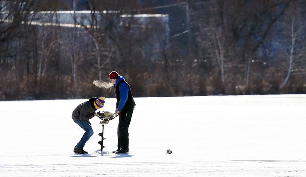 BEN GARVER — THE BERKSHIRE EAGLE<br /> Ice fishermen use a auger to drill a fishing hole on the Cheshire Reservoir, Thursday, December 27, 2018, Cheshire, Mass. The ice is 6 inches thick where the men are fishing, but open water exists near areas with current near the outlets; only experts should venture out on the ice.