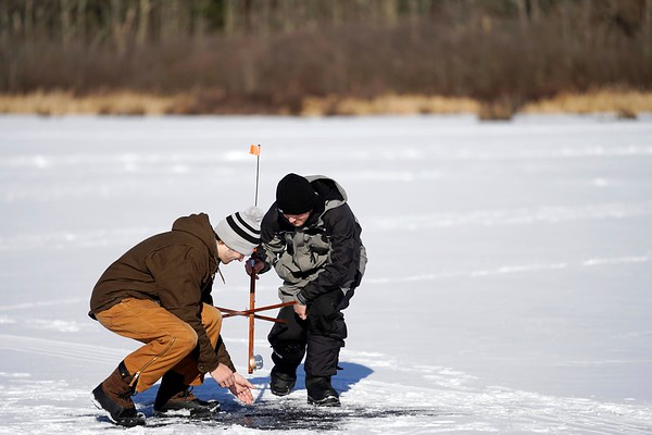 BEN GARVER — THE BERKSHIRE EAGLE<br /> Ice fishermen Andrew Koch and Corbin Richardson Check a fish trap on the Cheshire Reservoir, Thursday, December 27, 2018, Cheshire, Mass. The ice is 6 inches thick where the men are fishing, but open water exists near areas with current near the outlets; only experts should venture out on the ice.
