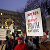 BEN GARVER — THE BERKSHIRE EAGLE<br /> Paul Brazie lights his protest sign with a flashlight as protesters hold up signs to traffic on Park Square in Pittsfield, Mass., supporting impeachment articles against President Trump to be passed in Congress, Tuesday, December 17, 2019.